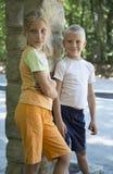 Kinder - Bruder und Schwester, die draußen, lächelnd steht Stockfotos