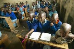 Kinder in den blauen Uniformen in der Schule hinter Schreibtisch nahe Nationalpark Tsavo, Kenia, Afrika lizenzfreie stockbilder