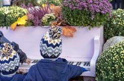 Kinder in den gleichen Hüten, die das Klavier im Herbstgarten spielen stockfotografie