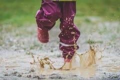 Kinder in den Gummistiefeln und in der Regenkleidung, die Pfütze defocus springt lizenzfreie stockbilder