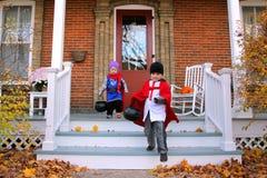 Kinder in den Kostümen, die auf Halloween Trick-oder-behandeln stockfoto