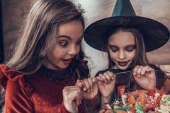 Kinder in den Kostümen, die voll Schüssel von Candys untersuchen stockfotografie