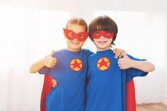 Kinder in den roten und blauen Klagen von Superhelden Sie in den Masken Kinder, die im hellen Raum aufwerfen Stockbilder