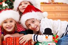 Kinder in den Weihnachtshüten Stockfoto