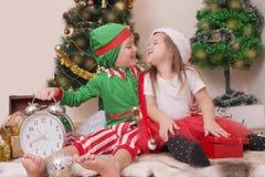 Kinder in den Weihnachtskostümen lachend mit Geschenken Stockfotos