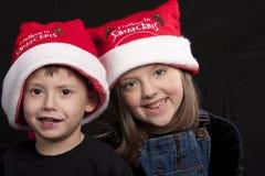 Kinder in den Weihnachtsmann-Hüten lizenzfreies stockbild