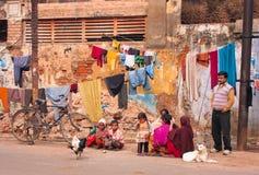 Kinder der armen Familie spielen im Freien nahe dem Dorfhaus mit trocknender Kleidung Lizenzfreie Stockbilder