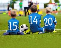 Kinder in der blauen Sportkleidung, die auf Fußball-Neigung und aufpassendem Spiel sitzt Lizenzfreie Stockbilder