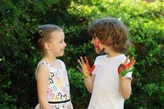 Kinder in der Farbe, Blick auf einander und Lächeln Stockbilder