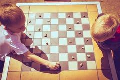 Kinder der kleinen Jungen, welche die Kontrolleure im Freien spielen stockbild