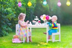 Kinder an der Puppenteeparty Stockfoto