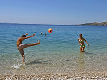 Kinder in der Spaßespritkugel auf Meer Stockfotografie