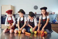Kinder in der Uniform von Köchen auf dem Tisch im Gemüse in t lizenzfreies stockfoto