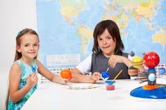 Kinder in der Wissenschaft und in der Kunstklasse - Malen des Modellbaus von Stockfotografie