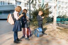 Kinder des grundlegenden Alters mit Smartphones, Rucksäcke, Hintergrund im Freien Ausbildung, Freundschaft, Technologie und Leute lizenzfreies stockfoto