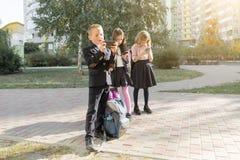 Kinder des grundlegenden Alters mit Smartphones, Rucks?cke, Hintergrund im Freien stockfotografie