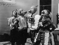 Kinder, die Äpfel auf Schnüren bei Halloween beißen (alle dargestellten Personen sind nicht längeres lebendes und kein Zustand ex stockbilder