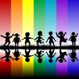 Kinder, die über einem Regenbogenhintergrund spielen Lizenzfreies Stockfoto