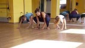 Kinder, die Übungen mit Trainer in einer Turnhalle tun stock footage