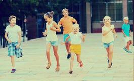 Kinder, die aktiv auf Straße auf Sommer d spielen und zusammen laufen lizenzfreie stockfotos