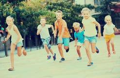 Kinder, die aktiv auf Straße auf Sommer d spielen und zusammen laufen lizenzfreie stockbilder