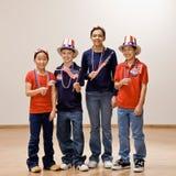 Kinder, die amerikanische Flagge anhalten und Hüte tragen lizenzfreie stockfotografie