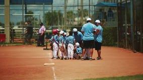 Kinder, die Anweisungen vom Trainer am Baseballspiel erhalten stock video