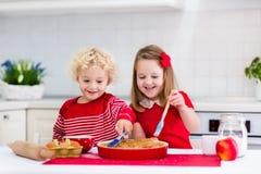 Kinder, die Apfelkuchen backen Stockbild