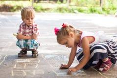 Kinder, die auf Asphaltfamilienhaus zeichnen Lizenzfreies Stockfoto