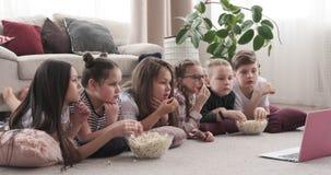 Kinder, die auf aufpassendem Film des Bodens liegen und Popcorn essen stock video footage