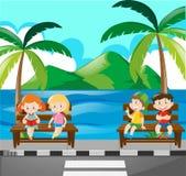 Kinder, die auf Bank durch das Meer sitzen Lizenzfreies Stockbild