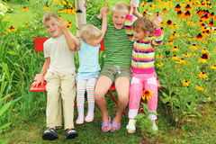 Kinder, die auf Bank im Garten sitzen Lizenzfreies Stockbild