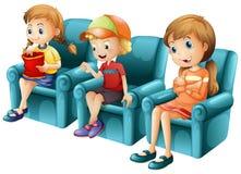 Kinder, die auf blauem Sofa sitzen Lizenzfreies Stockbild