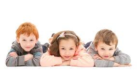 Kinder, die auf Boden legen stockbild