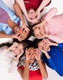 Kinder, die auf dem Boden Kopf-an-Kopf- mit Gläsern aus Fingern heraus liegen Stockfotografie