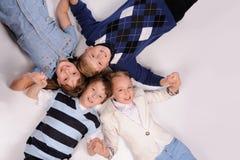 Kinder, die auf dem Boden liegen Stockbild