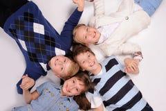Kinder, die auf dem Boden liegen Stockbilder