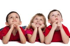 Kinder, die auf dem Boden liegen und oben schauen Stockfotos