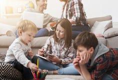 Kinder, die auf dem Boden während Eltern auf Sofa spielen Lizenzfreies Stockfoto
