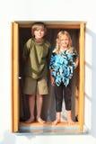 Kinder, die auf dem Fenster stehen Stockbilder