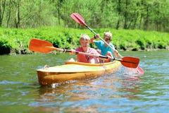 Kinder, die auf dem Fluss Kayak fahren Stockfotos