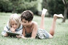 Kinder, die auf dem Gras schaut auf der Tablette liegen stockfotos