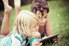 Kinder, die auf dem Gras schaut auf der Tablette liegen lizenzfreies stockfoto