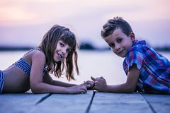 Kinder, die auf dem hölzernen Pier und dem Händchenhalten liegen stockfotografie