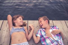 Kinder, die auf dem hölzernen Pier und dem Händchenhalten liegen lizenzfreie stockfotos