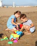 Kinder, die auf dem Strand spielen Lizenzfreies Stockbild