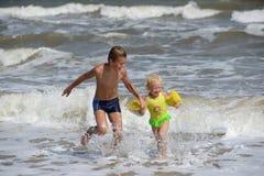 Kinder, die auf dem Strand spielen Lizenzfreies Stockfoto