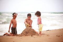 Kinder, die auf dem Strand spielen Stockfotografie