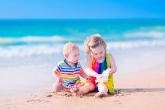 Kinder, die auf dem Strand spielen Lizenzfreie Stockbilder