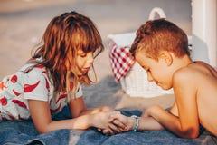 Kinder, die auf dem Strand und dem Händchenhalten liegen stockbilder